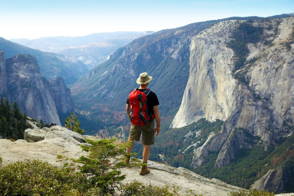 Wanderer blickt vom North Dome ins Yosemite Valley, Yosemite-Nationalpark, Kalifornien Reise Wanderer blickt vom North Dome ins Yosemite Valley, Yosemite-Nationalpark, Kalifornien 2020